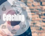 Kreis mit dem Wort Coaching in der Mitte vor Ziegelwand.