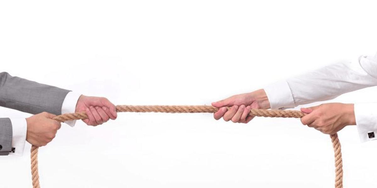 Zwei Menschen ziehen an beiden Enden von einem Tau.