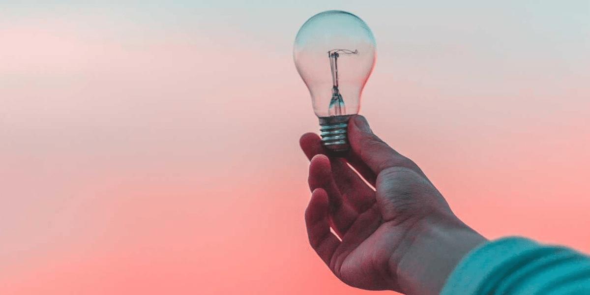 Person die eine Glühbirne vor einen rosa-blauen Hintegrund hält.